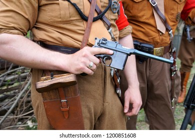 Sholokhovo, Moscow reg./Russia - May 5, 2018: A participant in the brown Nazi uniform holding a Mauser pistol at reenactment of one of the last battles of World War II - Battle of Courland.