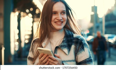 Shoot of beautiful european blondehair girl walking down the street, smiling, using phone, chatting with friends, looking around, feeling happy, having fun. Rays of the sun