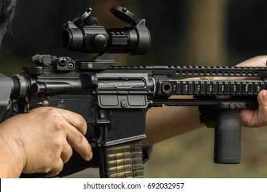 Shooter aiming assault rifle at target.