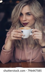 shooting in the coffee shop, the portrait of a young woman through the window, with coffee in hand