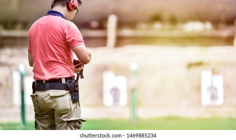 Shooting competition in the shooting field and men shooting a pistol..