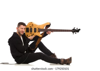Shooting guitarist. Male guitarist pretend shooting, holding and aiming bass guitar. Full length studio shot isolated on white.