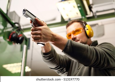 Shooting a gun at a shooting range.