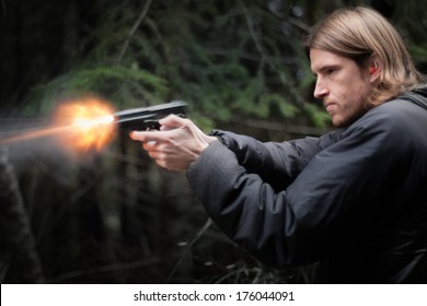 shooting a handgun and flames coming out of barrel.