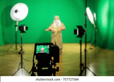 Shooting the movie on a green screen. The chroma key. Studio videography. Actor in theatrical costume. The camera and lighting equipment.