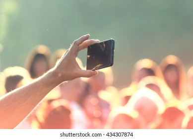 Shooting photos with a mobile phone in a crowd