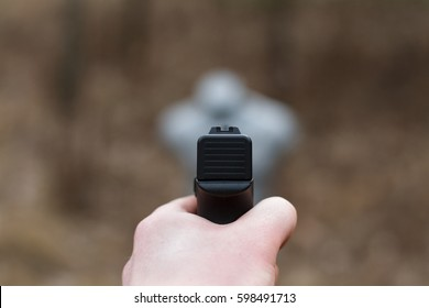 Shooting from a pistol. Reloading the gun. The man is aiming at the target. Shooting range. Man firing.