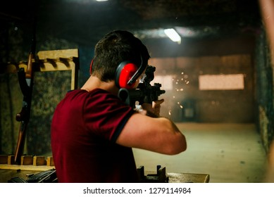 Shooting a pistol at target in indoor firing range or shooting range