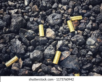 Shooting range concept. Five gold bullets on the little black stone ground after the shooter fired the gun. Selective focus.