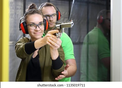 Shooting range. Shooting with a gun. The woman shoots from the gun at the shooting range under the supervision of an instructor.