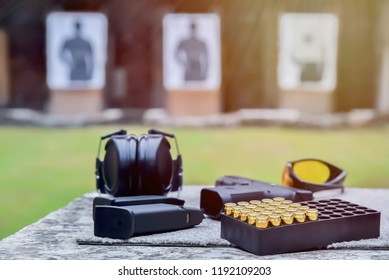 Shooting range. Shotguns, ammunition, ear plugs, and accessories for taking pictures on the table during shooting and shooting targets.