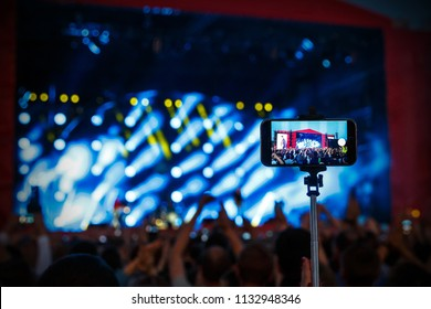 Shooting rock concert by smartphone on selfie stick monopod