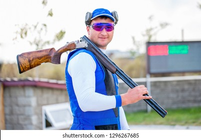 Shooting Sports. team workouts, shooting at a flying target. A man shoots a double-barreled shotgun at a sports shooting range, shooting at moving targets.