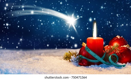 Shooting star Christmas background with a burning candle on a snowy twilight winter sky with falling snowflakes and copy space for your greeting