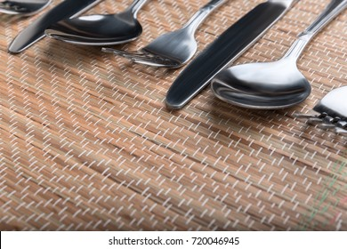 Shooting in the Studio .Forks,spoons and knives laid out in a row of light brown tablecloths made of straw.Top view-side view