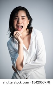 Shooting studio portrait of young Asian Thai woman with white shirt on white background. Relax and mordern concept.