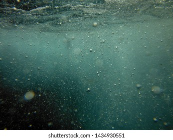 Shooting from underwater of a waves and bubbles witch creates in water of the see