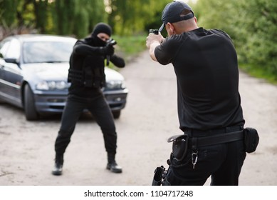Shootout between a police officer and a offender. Stop Terrorism and Crime. The police officer and the terrorist are aiming each other.