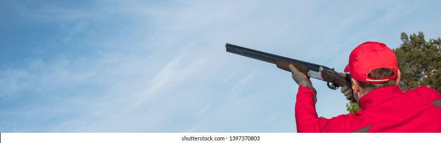 shoots skeet on a trench stand with a shotgun man skeet and trap shooting outdoors; shooting clay pigeon targets at gun club with airborne casing