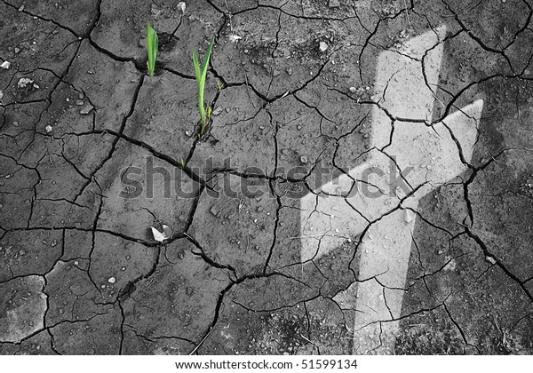 Shoots sprout up through dry earth in the Shadow of a cross in religious and perseverance concept