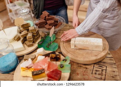 Shop assistant cutting bars of natural soap for customer in package free store. Display of colorful handmade organic soaps in packaging free shop.