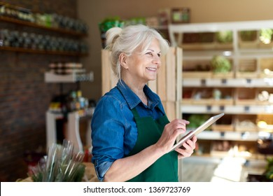 Shop assistant with digital tablet in small grocery store
