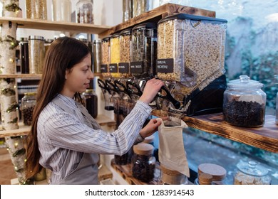 Shop assistant filling reusable bag with dried pasta in organic grocery store. Young shopkeeper working in zero waste shop.