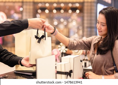 Shop assistant handing shopping bag to female customer.