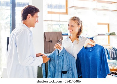 shop assistant helping to choose clothes in a store