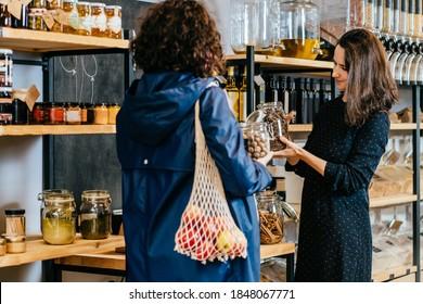 Shopassistent hilft Kunden im Massengütergeschäft. Verkäufer berät Frau beim Kauf von Lebensmitteln ohne Plastikverpackung in der Müllerei Null. Nachhaltiges Einkaufen in kleinen lokalen Unternehmen.
