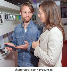 Shop assistant helping a customer choosing a phone