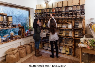 Shop assistant helping customer in packaging free shop. Zero waste shopping - woman buying fresh produce at package free grocery store.