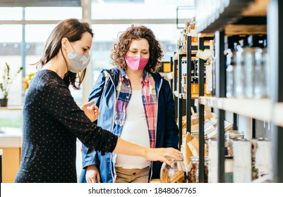 Shop assistant helping pregnant woman in bulk food store. Seller advising customer in her purchase of groceries without plastic packaging in zero waste shop. Support small local businesses.