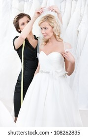 Shop assistant helps to the bride to fix the wedding veil