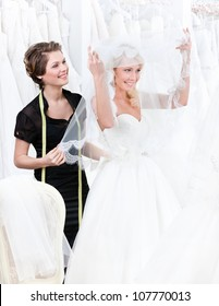 Shop assistant helps to the bride to put the wedding gown on. Bride raises the veil