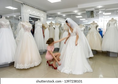 Shop assistant helps bride with wedding dress in boutique