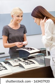 Shop assistant helps lady to choose jewelry at jeweler's shop. Concept of wealth and luxurious life