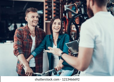 Shop Assistant Helps Young Couple in Bike Store. Seller Holds Instruction or Catalog with Different Bikes and Details and Advice Smiling Man and Happy Woman in New Bicycle Choosing