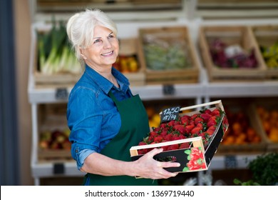 Shop assistant holding box with fresh strawberries in organic produce shop