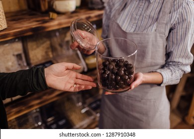 Shop assistant holding glass jar with healthy chocolate balls in organic store. Zero waste shopping - hand of customer pointing at fresh sweets in package free food store.
