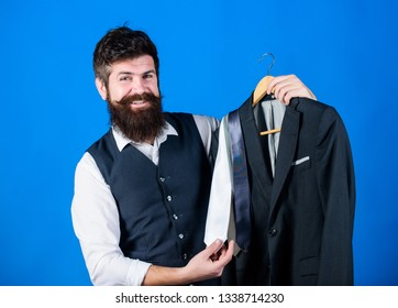 Shop assistant or personal stylist service. Matching necktie outfit. Man bearded hipster hold neckties and formal suit. Perfect necktie. Shopping concept. Stylist advice. Difficulty choosing necktie.