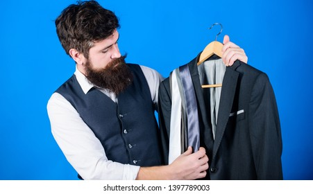 Shop assistant or personal stylist service. Matching necktie with outfit. Man bearded hipster hold neckties and formal suit. Guy choosing necktie. Perfect necktie. Shopping concept. Stylist advice.