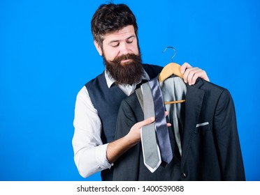 Shop assistant or personal stylist service. Stylist advice. Matching necktie with outfit. Man bearded hipster hold neckties and formal suit. Guy choosing necktie. Perfect necktie. Shopping concept.