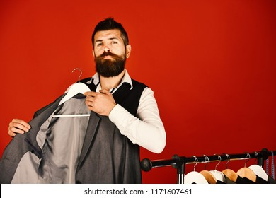 Shop assistant or seller puts grey suit on clothes hanger. Man with beard in vest by clothes rack. Businessman with proud face near jackets on red background. Official wardrobe choice concept.