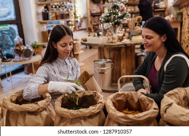 Shop assistant serving customer in packaging free shop. Zero waste shopping - woman buying fresh food at package free grocery store.