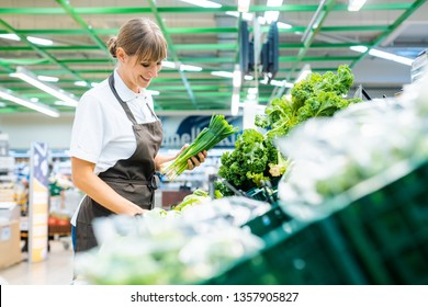 Shop assistant in supermarket re-stocking fresh vegetables into boxes