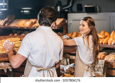shop assistants arranging loafs of bread in supermarket