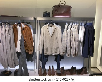 Shop of clothes,pants, coat, sundress,jacket and black and white shirts on hanger