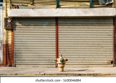 shop exterior with closed shutters, street facing store, sidewalk and hydrant