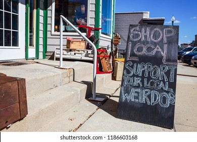 Shop local saturday, support your local weirdos, humorous sign written in chalk, supporting small local businesses